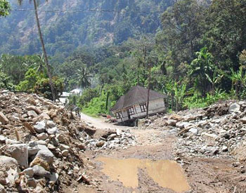 A collapsed house on the road around the lake