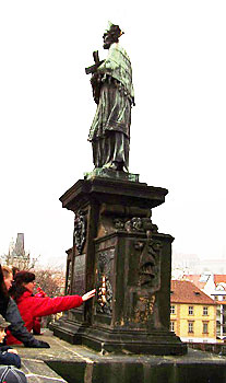 A visitor touches the plaque on the right beneath St. John of Nepomuk's statue.
