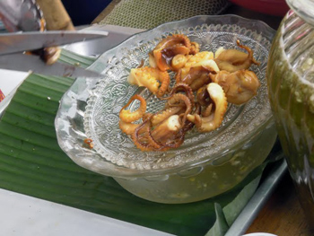 Squid, cut up with scissors, is a popular street food in Thailand.