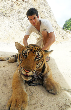 Crouching beside a fully grown male tiger inside the Tiger Temple. My facial expression tells the reader exactly how nervous I was! Photo by Joseph Lobo