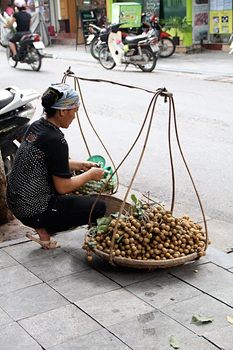 A vendor with her le thung at rest.