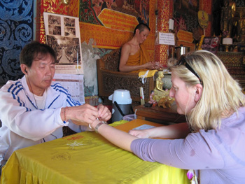Receiving my blessing at Doi Suthep Temple from the Monks' helper as the Monk is not allowed to touch or to be touched by a woman.
