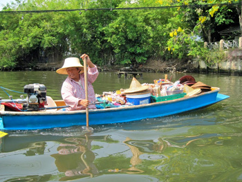This woman has a floating market on her boat. She sells cold beverages, postcards, and straw hats to passing boats.