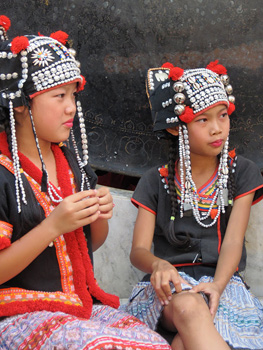 Young girls gather in traditional Hill Tribe headdresses at Doi Suthep Temple.