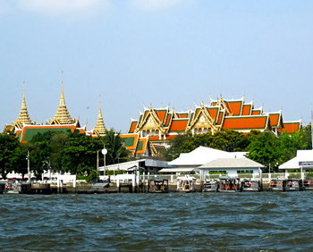 The gold flake paint and the orange roof of The Grand Palace can be seen from my long-tailed boat on the Chao Phraya River.