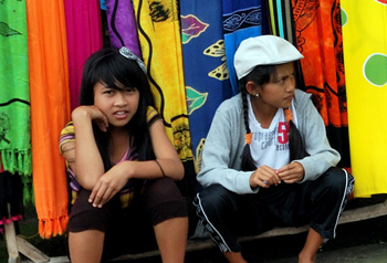Girls selling sarongs in front of a temple