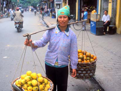 A radiant young lady sells mangoes and oranges in Hang Bo Street.