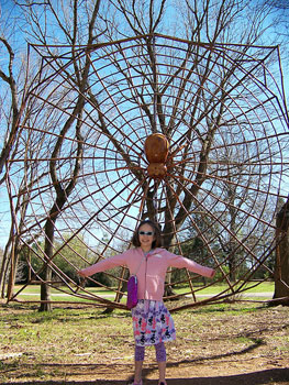 Spider sculpture and the author's daughter at the Huntsville Botanical Garden