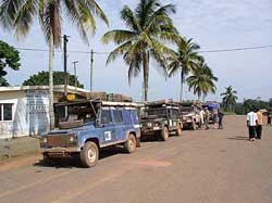 Arriving in Bakoumba, Gabon. Our 'overland' vehicles lined up along the main street as we search for the immigration official and enjoy cool drinks purchased from a local vendor.