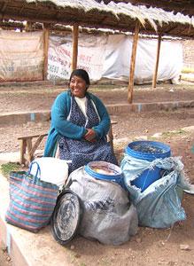 A vendor at the bazaar in Chinchero stays warm behind her bucket of chicha de jora (fermented corn homebrew).