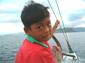 """Eko, our boat captain's son, plays in the wind on board a """"klotok"""" during our two-day trip."""