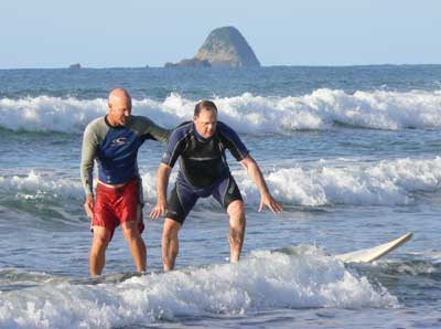 Greg Page of Hang 20 Surfing, helps Max get up on the board.