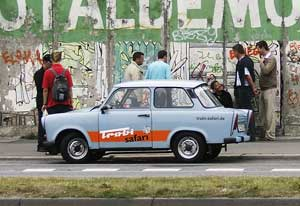 "A ""Trabi"" from Berlin's Trabant Safari parked alongside The East Side Gallery."