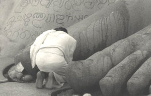 A priest at the foot of Lord Bahubali's statue