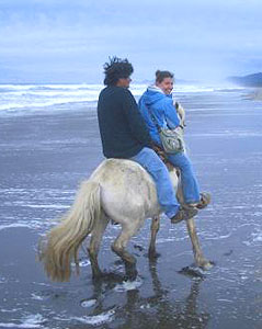 Anna and Nelson riding horseback on the beach in Chiloe, Chile