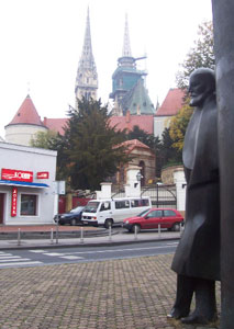 The legendary Croatian writer and poet, Mugust Senoa, takes a rest against a newsstand with the spires of the Cathedral of the Assumption of the Virgin Mary and St. Stephen rising in the background.