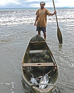 Fisherman near Rio Jovi, Colombia. Everyone uses dugout canoes and they row as far as two kilometers off shore to catch fish with lines, not nets. Photos by Max Hartshorne.