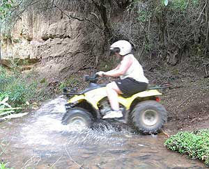 An adventurer rides her quad bike through a stream near the Swartberg Mountains. Photo by Carly Blatt