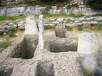 Shaft graves and stelae of the Mycenean Grave Enclousure. You can see the remains of the enclousure wall behind the graves.