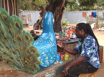 Coffin craftsman putting finishing touches on a peacock coffin.