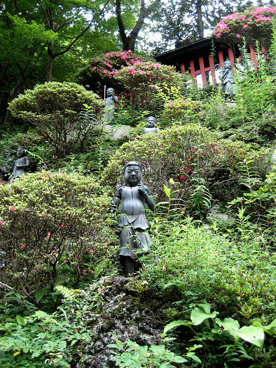 Statues hiding in the shrubbery around the Yakou-in Shrine in Tokyo