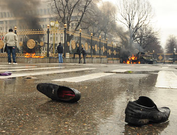 A pair of shoes left on the street after a body has been carried away in Bishkek, Kyrgyzstan, in April, 2010. In the background is a burning truck.