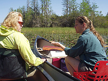 Joy Campbell shows an Okefenokee visitor a plant while on the water trails