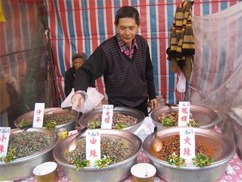 Snails for sale! Markets offer all sorts of interesting snacks.