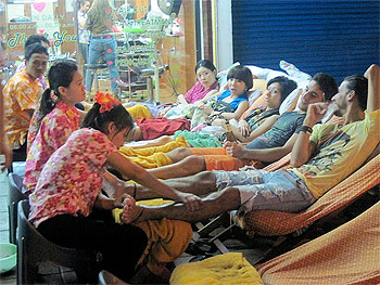 A group of people take a break and get a foot massage while the craziness of the Songkran Festival goes on around them.