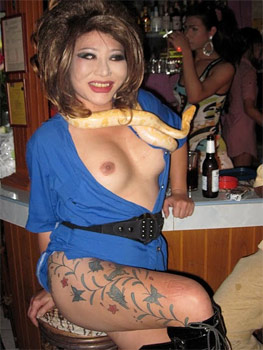 Marina, from Marina's Lady Boy Bar in Chiang Mai, poses with her new breasts and her albino python snake.