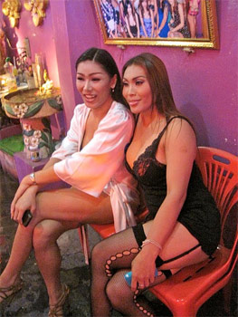 "Two very attractive ""lady boys"" pose for a photo outside of the 'G-SPOT' nightclub at Soi Cowboy in the red light district in Bangkok."