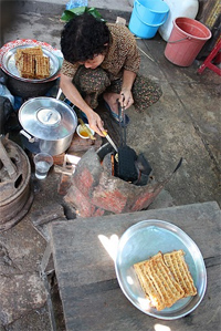 A vendor at the Kampot market makes coconut waffles on a griddle greased with coconut oil.