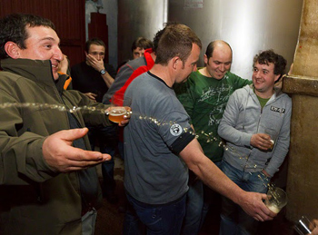 Txotx! drinking from the barrel at a Basque cider house. photo by Paul Shoul.