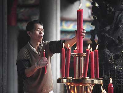 A man lights prayer candles at the Tienhou Temple in Tainan.
