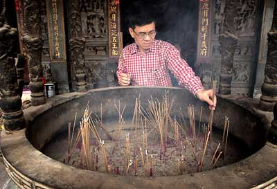 Man lighting incense at the Tienhou Temple