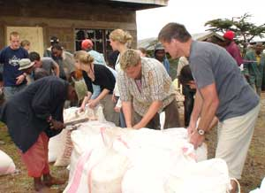 Mark helps distribute food to waiting villagers.
