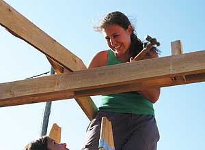 lejandra Olivera hammers the beams into place for a house in Montevideo, Uruguay. Photos by Jon Brandt
