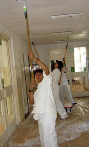 Noor Che'ree helps paint the inside of a school in Poland.