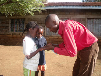 Armstrong O'Brian Ongera, Jr., Executive Director of the AID Kenya Foundation with two children at the Wanalea Children's Home