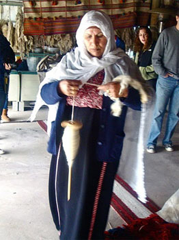 Woman of the Laquiya Weaving Project, working on a rug