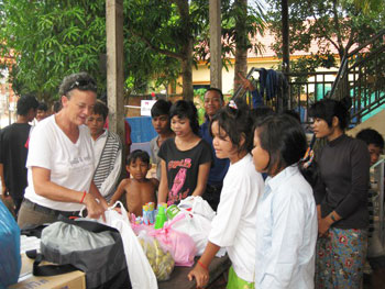 Lori Carlson hands out donations at a Siem Reap children's shelter. Photo by Shelley Seale