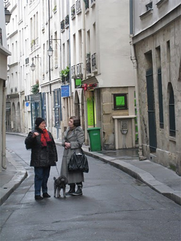 The neighbors chat on a street in Paris.