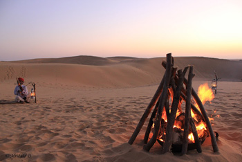 The musician and the bonfire at dusk, Lakhamana Sand Dunes, Jaisalmer,, Rajasthan