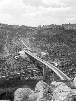 A settler road in the West Bank. The local Palestinian road curves underneath.