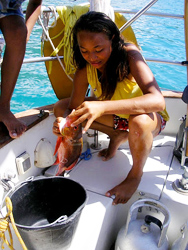 A Marquesan girl demonstrates how to scale and gut a red snapper.
