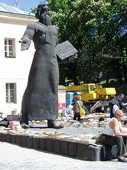 An outdoor bookmarket in Lviv beneath a monument to Ivan Fedorov, the city's first printer