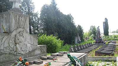 In a town cemetery, a monument to the Sich Riflemen stands beside a monument to Soviet dead from WWII.
