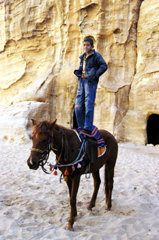 A boy shows off his riding skill in Little Petra, Jordan.