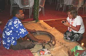 A tribal chief in Fiji shares kava with a visitor.