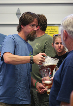 Brewmaster at Grand Teton brewing pouring suds for guests.